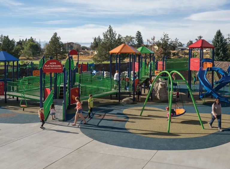 Inclusive playground with rubber surfacing for accessibility.